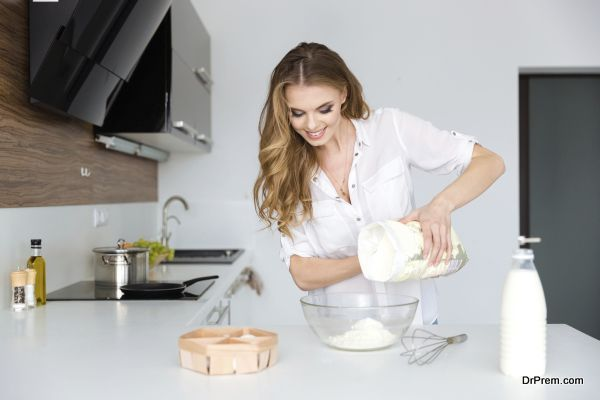 Smiling beautiful young woman preparing dough on the kitchen