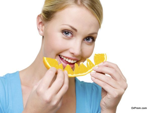 Attractive smiling woman eats the fresh orange - over white background