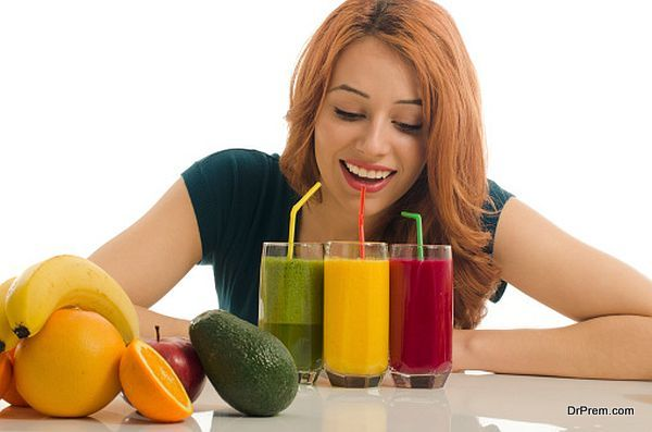 Happy woman holding in front of her three different smoothie