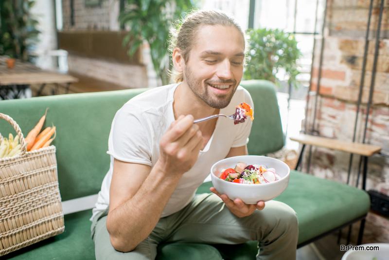 Handsome man eating healthy salad